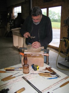 Bill Doub seen carving lotus blossom, with credenza case under construction in background.