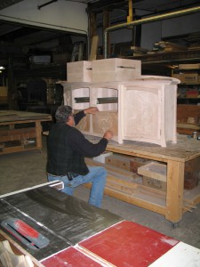 Bill is seen fiting the carved doors into the lotus credenza.