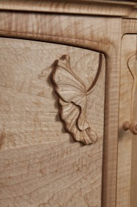 Hanging lotus carving in place on file drawer.